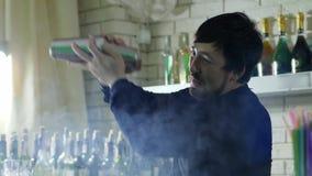 Grabbbartendern med shaker i hand blandar ingredienser på bakgrundsflaskor i rök lager videofilmer
