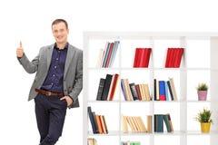 Grabbbenägenhet på en bokhylla och ge upp en tumme Royaltyfri Bild