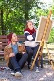 Grabbblickarna som en flicka drar en målare arkivfoto