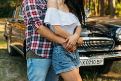 grabben är behind och kramar flickan, räcker tillsammans bak är en svart bil rymma händer i sommaren på handen av en grabb som bä Royaltyfri Foto