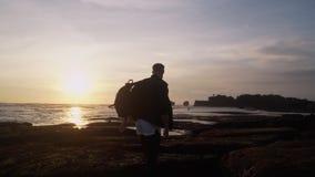 Grabben öppnar hans armar som är breda mot härlig guld- solnedgång på stranden, uttrycker avkänning av frihet, happines arkivfilmer