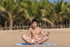Ockupationar vid yoga på en strand Fotografering för Bildbyråer