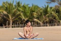 Ockupationar vid yoga på en strand Arkivbild