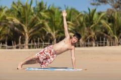 Ockupationar vid yoga på en strand Arkivfoto