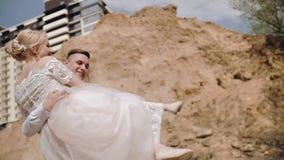 Grabben cirklar hans flickvän i hans armar Flickan har en härlig vit klänning och en bukett av blommor i hennes händer Bra M stock video