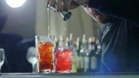 Grabben förbereder coctailar och häller gin från grej in i drinken med is i exponeringsglas på räknare i dimmanärbild lager videofilmer