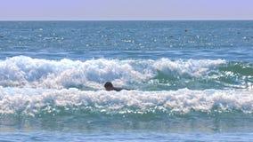 Grabben försöker att stå på surfingbrädan i liten våg lager videofilmer
