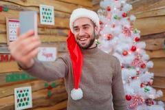 Grabben gör en selfie med ett dekorerat träd i rummet fotografering för bildbyråer