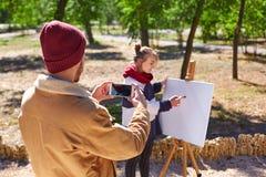 Grabben gör ett foto hur en ung konstnär arbetar Arkivfoton