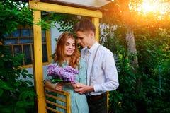 Grabben ger hans flickvän en bukett av lilor, henne kom ut ur porten arkivbilder