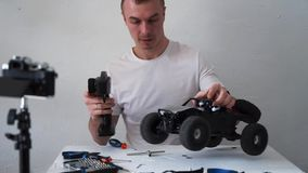 Grabben h?ller en video blogg om radion kontrollerade bilmodeller P? tabellen ?r hj?lpmedel f?r reparation stock video