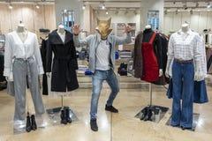 Grabben i den djura maskeringen i ett klädlager bredvid huvudlösa skyltdockor Begreppet av shopping och mode En rolig bild arkivfoto