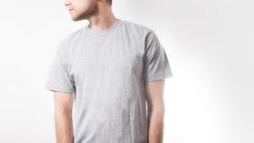 Grabben i den tomma gråa t-skjortan, ställning som ler på en vit bakgrund, åtlöje upp, fritt utrymme, logo, design, mall för desi Arkivfoton