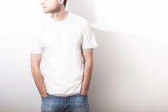 Grabben i den tomma vita t-skjortan, ställning som ler på en vit b Arkivfoto