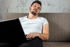 Grabben i den vita skjortan som sitter på soffan, avverkar sovande på arbete på en bärbar dator Begreppet av indolens, apati arkivfoto