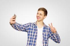 Grabben i en blå skjorta gör en selfie på telefonen, lycklig man, arkivbild