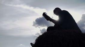 Grabben i en rutig skjorta spelar på ett gitarrsammanträde i ett fält på en höstack arkivfilmer