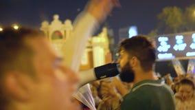 Grabben i grön T-tröja jublar på högtalaren för fotboll för gatapartiet den vinnande lager videofilmer