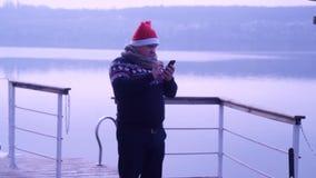 Grabben i hatten av jultomten talar på telefonen arkivfilmer