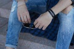 Grabben i jeans rymmer exponeringsglas handen för man` s rymmer exponeringsglas Royaltyfria Foton