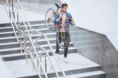 Grabben i jeansomslaget som på bär hans orange cykel för skuldra arkivfoton