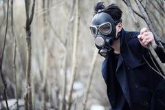 Grabben i laget och gasmasken Stolpe-apokalyptisk stående av A Arkivfoto