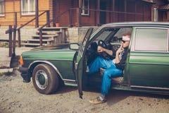 Grabben i ninetiesna sitter bak hjulet av en bil som röker en cigarett Royaltyfria Bilder