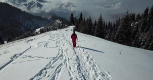 Grabben i skidar dräkten är på en snöig slinga i bergen ovanför oklarheter lager videofilmer