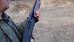 Grabben kastar hagelgeväret framme av honom Grabben får klar att skjuta på skjutbanan arkivfilmer