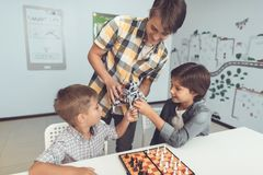 Grabben kom med två borrade pojkar en grå robot Bredvid dem ställningar en schackbräde med schackstycken Arkivbilder