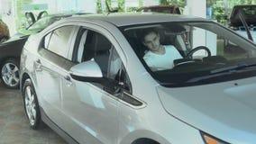 Grabben kontrollerar bilen från inre för köpet det i bilåterförsäljare lager videofilmer