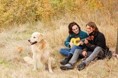 Grabben lär att spela en flicka på gitarrsammanträde på en sängöverkast i höstgläntan fotografering för bildbyråer