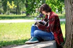 Grabben lärer att play gitarren Arkivfoton