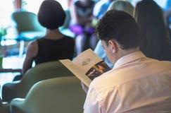 Grabben läser en bok på en konferens royaltyfria bilder