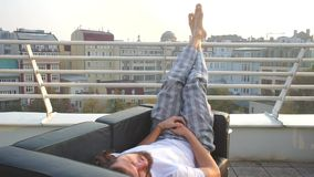 Grabben ligger på soffan, lägger benen på ryggen upp, balkongen stock video