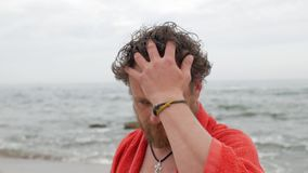 Grabben med ett sk?gg och bl?a ?gon p? bakgrunden av havet med en handduk p? hans skuldror ser in i kameran, v?nder hans huvud stock video