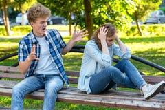 Grabben med flickan på bänk Begreppet av agression i ett förhållande Skandal i familjen Grabben skriker på arkivfoto