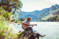 Grabben med gitarren vid floden Fotografering för Bildbyråer
