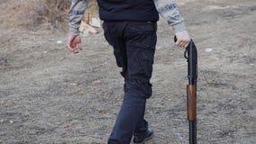 Grabben med hagelgeväret i hans vänstra hand går till den avfyra positionen Närbild bak hans ben och armar arkivfilmer