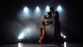 Grabben med handskar för en flickaboxning som slår i cirkeln i mörkret, förbereder sig de för en kickboxing konkurrens arkivfilmer