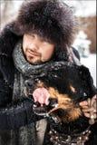 Grabben med hunden i parkera i vinter snowing Arkivbild