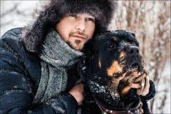 Grabben med hunden i parkera i vinter snowing Royaltyfria Bilder