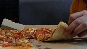 Grabben med skägget tar ett stycke av pizza i hans hand och biter pizza 4K video 4K arkivfilmer