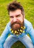 Grabben med svalört blommar i skägget som tar selfiefotoet Hipster med den ilskna grimasen på framsidan som tar selfiefotoet fotografering för bildbyråer