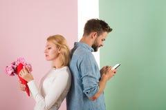 Grabben med telefonen och flickan med buketten blommar, pastellfärgad bakgrund Fuskbegrepp Smsande vän för manhållsmartphone arkivbilder