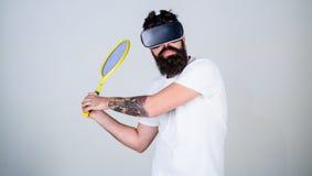 Grabben med VR-exponeringsglas spelar tennis med racket och klumpa ihop sig Mannen med skägget i VR-exponeringsglas spelar tennis Royaltyfri Bild