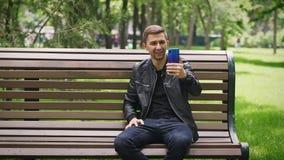 Grabben meddelar på video pratstund via smartphonen stock video