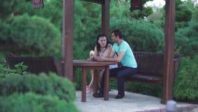 Grabben och en flicka sitter i parkera lager videofilmer