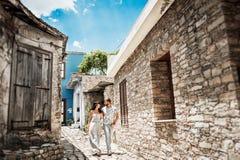 Grabben och flickan går till och med de gamla gatorna av staden arkivbild