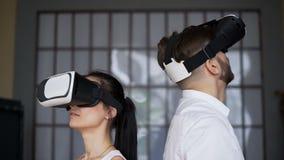 Grabben och flickan i moderna VR-exponeringsglas ser omkring arkivfilmer